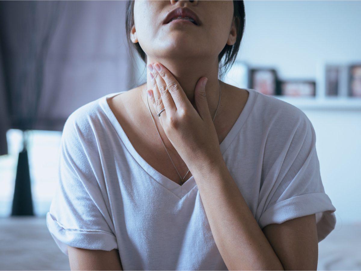 Woman holding throat weak voice