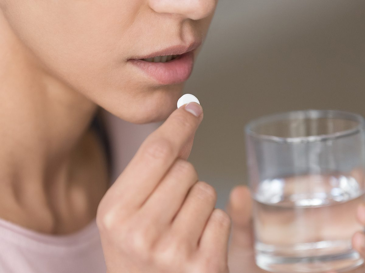 Woman taking pill - prescription drugs interaction with supplements