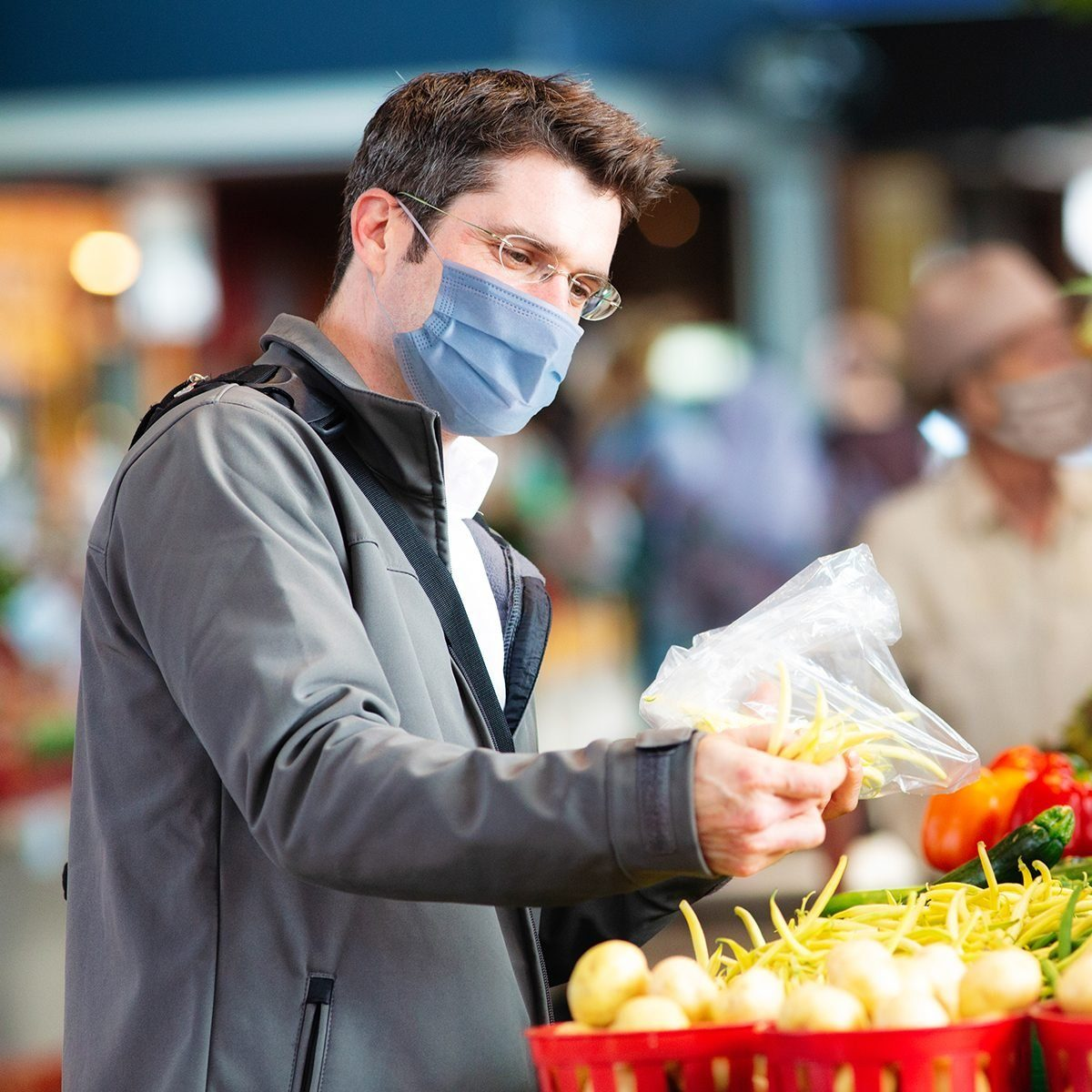 Young man wearing face cover selecting string beans at farmer's market to prevent spreading the covid 19 virus.