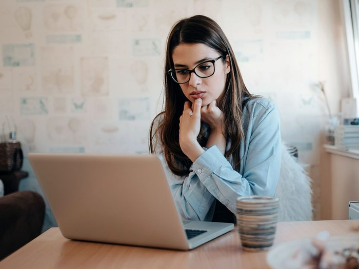 Woman looking at Apple computer, scared of suspicious scam email from Apple Support