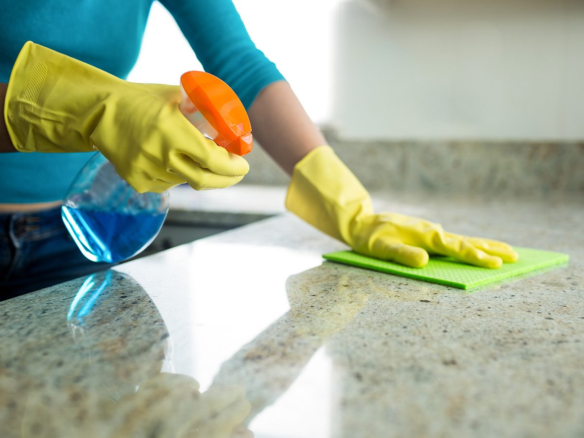 Never use a Magic Eraser to clean these things - Woman cleaning countertop