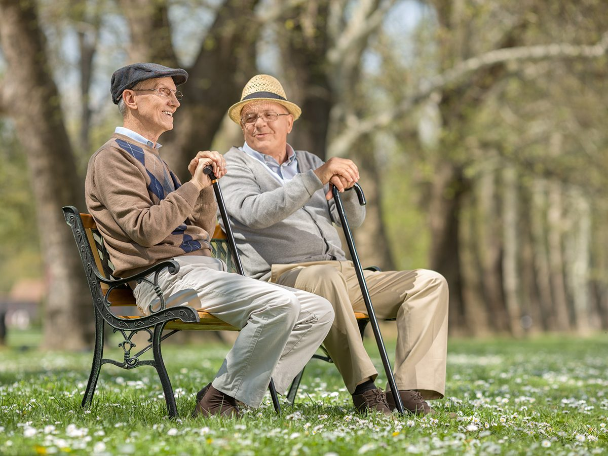 Capricorn Trust - Two old friends sitting on a wooden bench in park and talking to each other