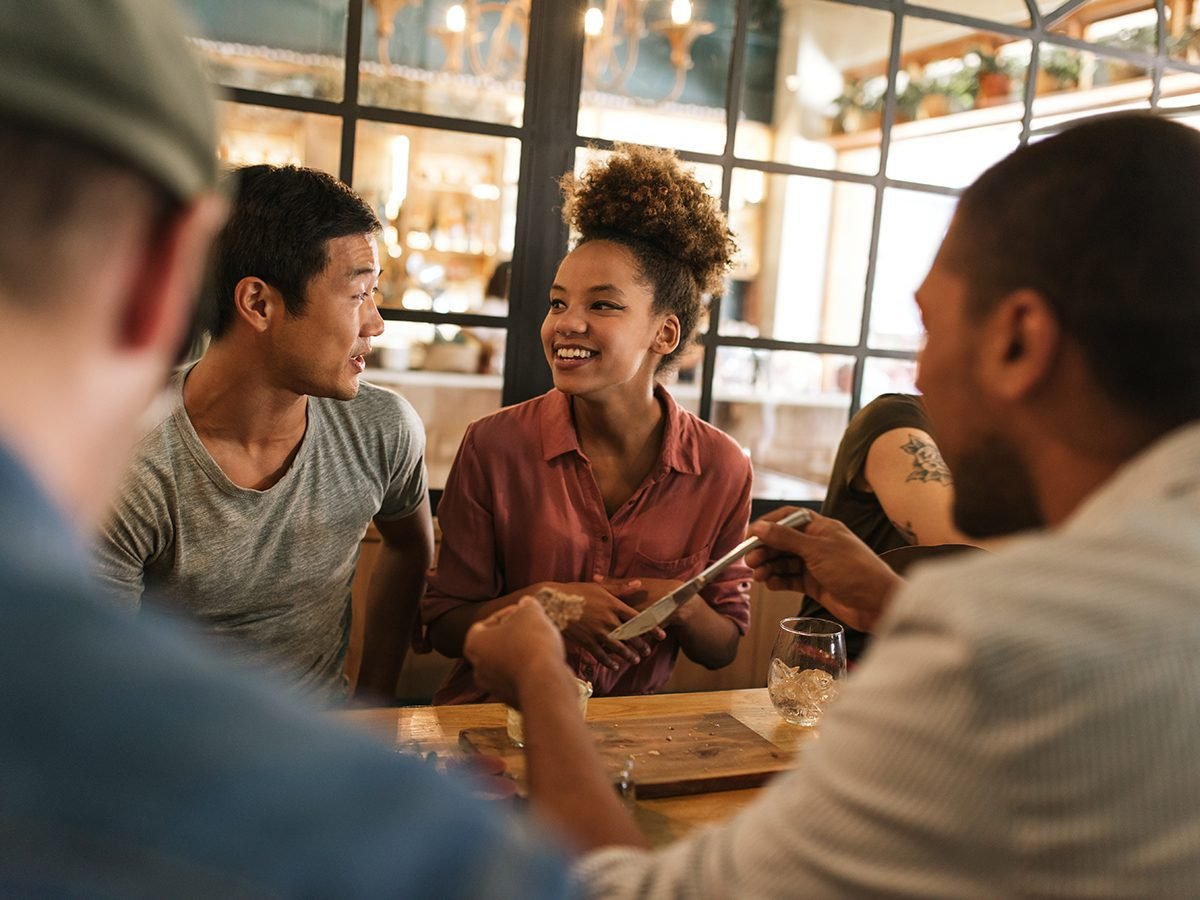 Libra Trust - group of smiling young friends sitting at a table in a bistro talking together over a meal