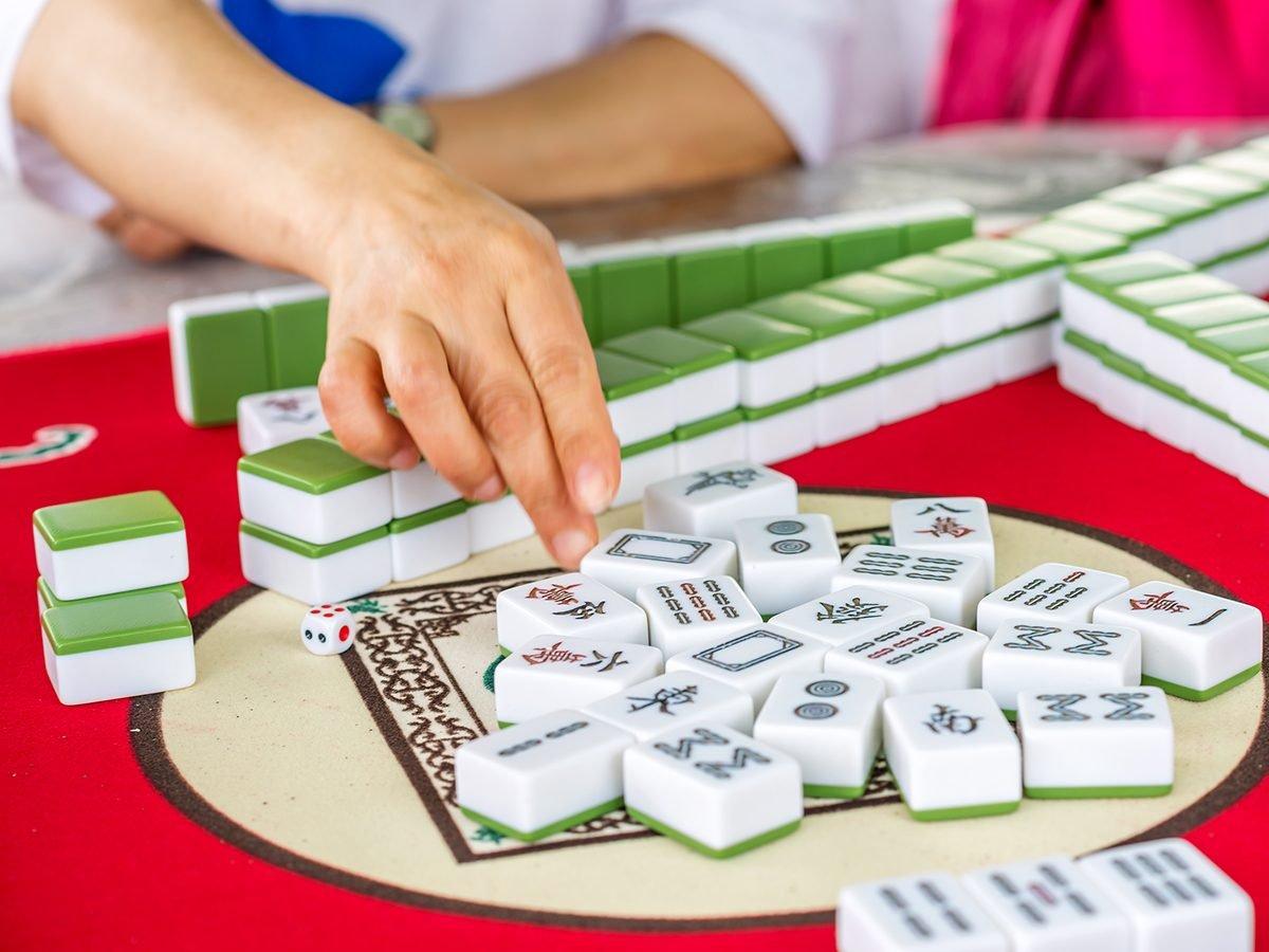 Mahjong Facts - Person playing mahjong at table