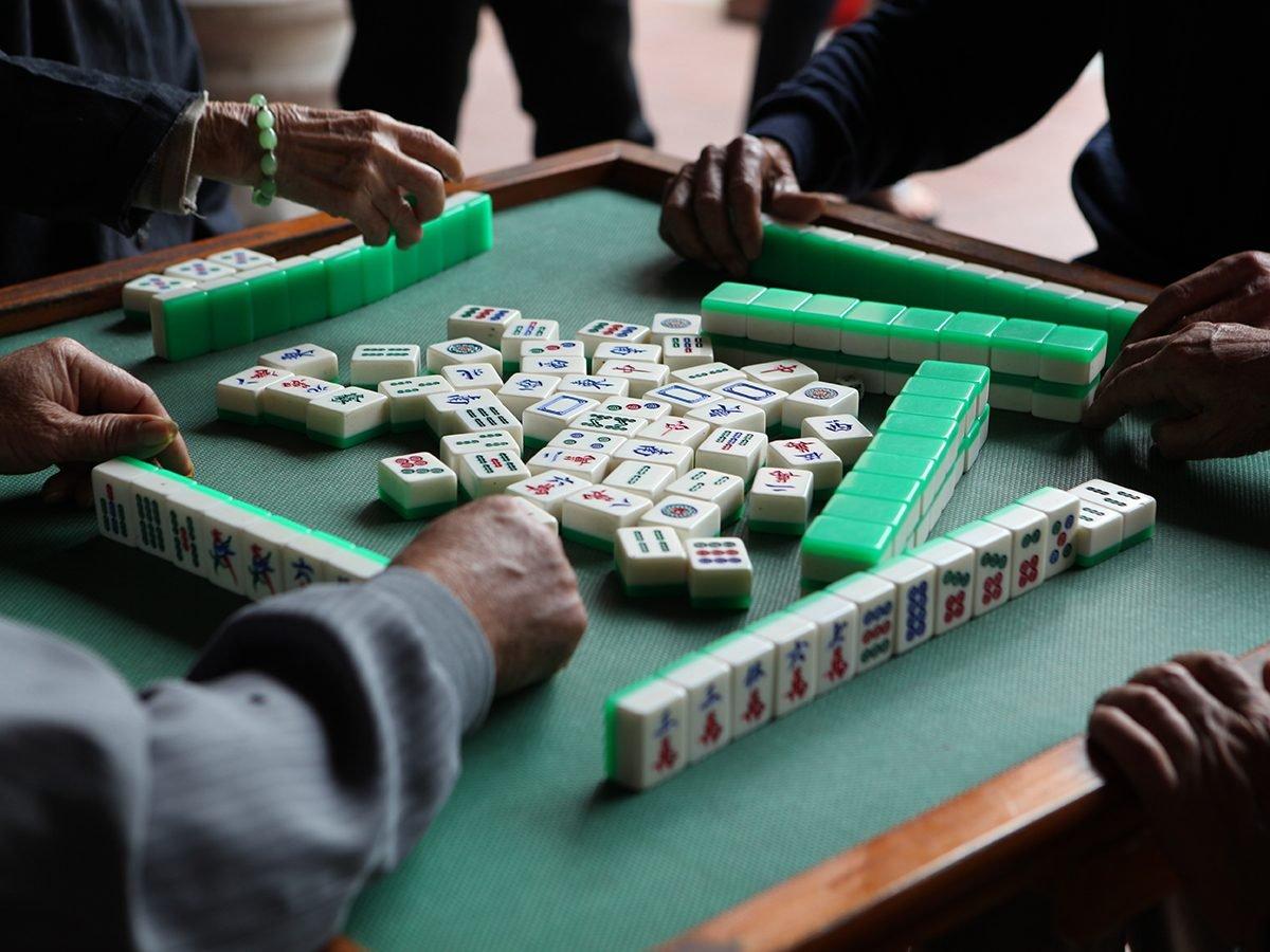 Mahjong Facts - Group of people playing mahjong at table
