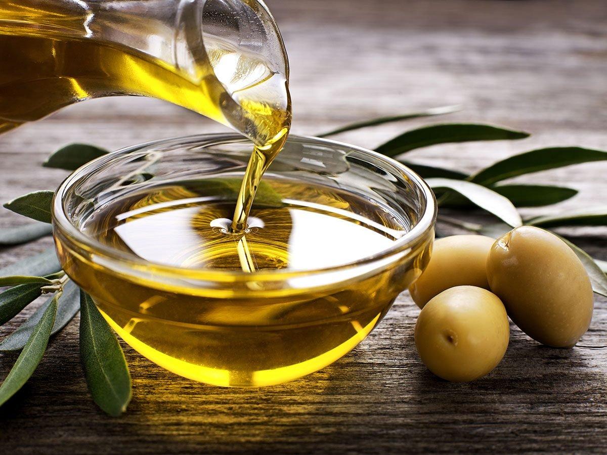Bottle pouring virgin olive oil in a bowl.