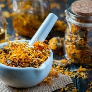 folk medicine remedies - Calendula flowers in stone mixing bowl.