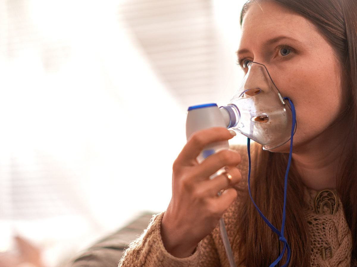 woman makes inhalation nebulizer at home. holding a mask nebulizer inhaling fumes spray the medication into your lungs sick patient. self-treatment of the respiratory tract using inhalation nebulizer