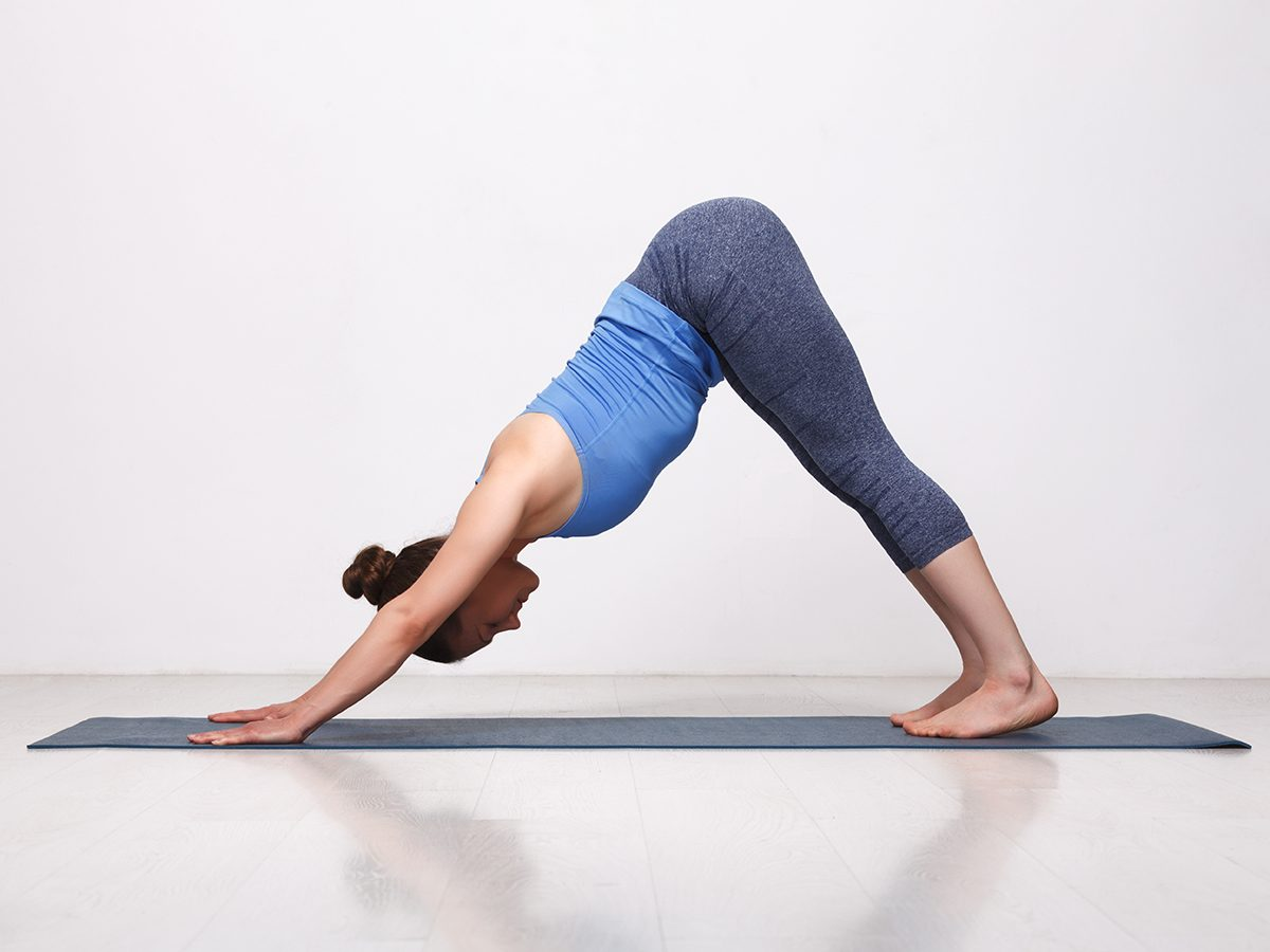 Woman practices yoga asana adhomukha svanasana - downward facing dog pose in studio