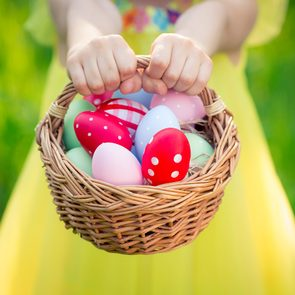 Child holding basket with Easter eggs outdoors in spring park