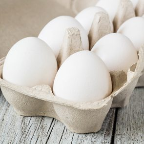Cardboard egg rack with eggs on white wooden table