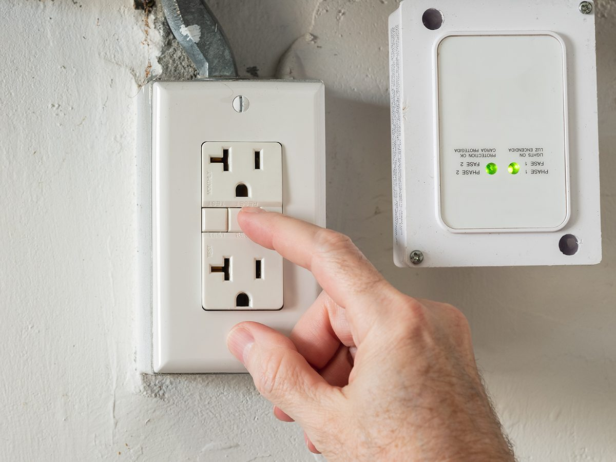 Closeup of hand resetting tripped GFI electricity outlet. Residential gfci ground fault interrupter electric socket plug and wall plate.