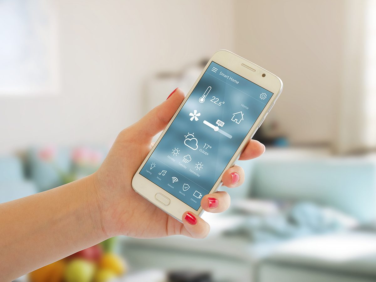 Smart home control of temperature, safety and environment in home. Mobile app on display. Living room in background.