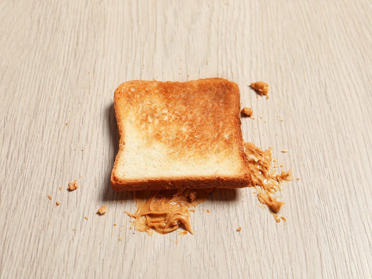 Overturned toast bread with peanut butter on floor