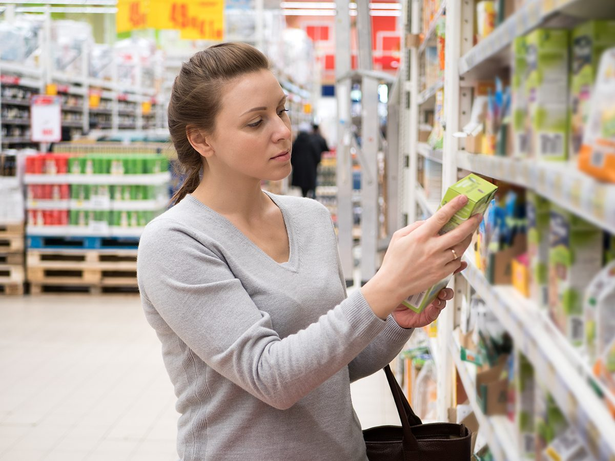 Too much salt - woman reading nutrition label