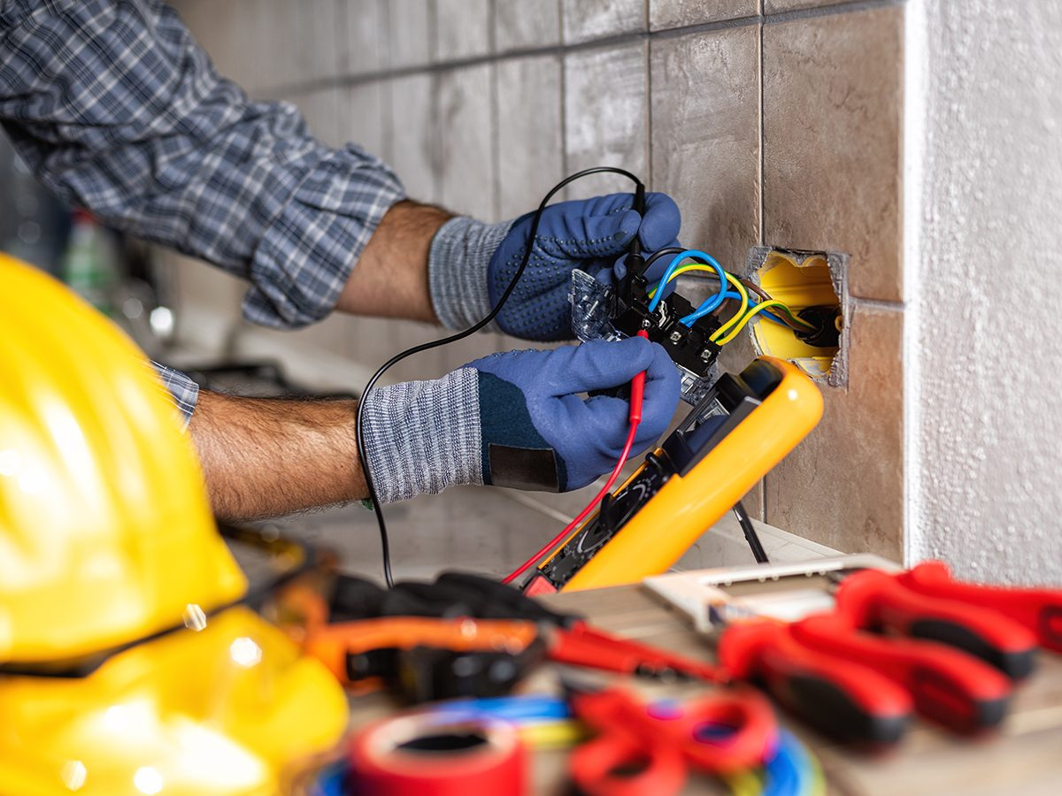 Electrician at work with the tester measures the voltage in the sockets of a residential electrical system. Construction industry.