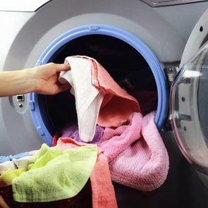 Hand putting clothes in wash/dryer machine