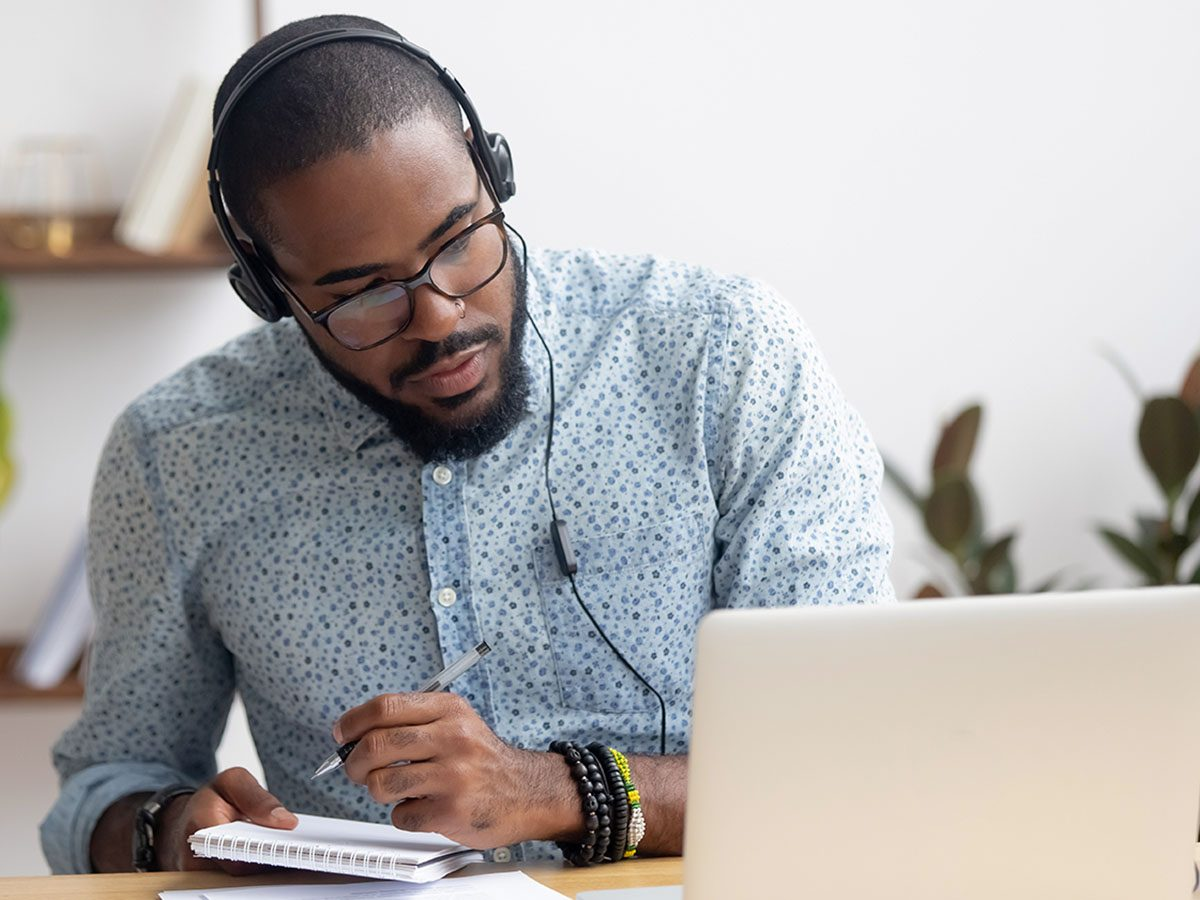 business man in headphones writing notes in notebook watching webinar video.