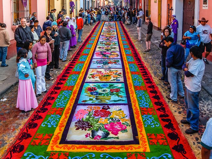 Easter Traditions Antigua - Locals & tourists admire dyed sawdust carpet made overnight for Good Friday procession in Antigua, Guatemala