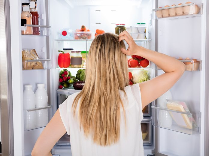 How To Organize Your Fridge - woman standing in front of open fridge