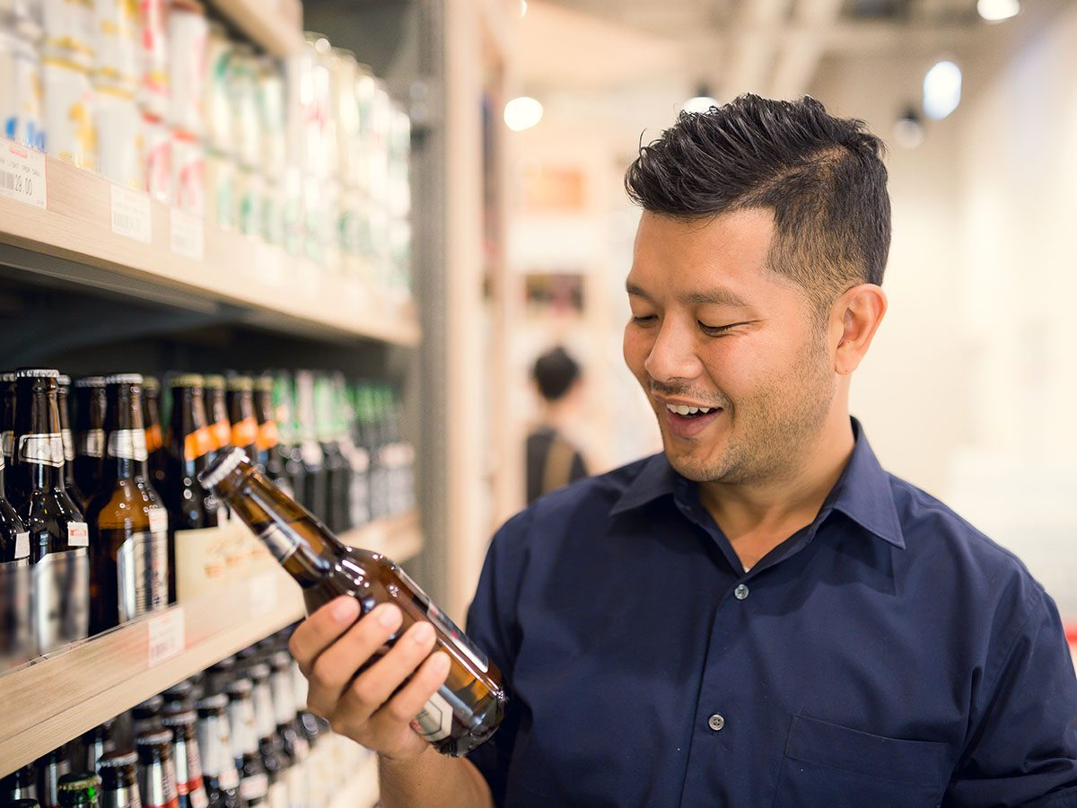 man happy selecting a beer from supermarket.