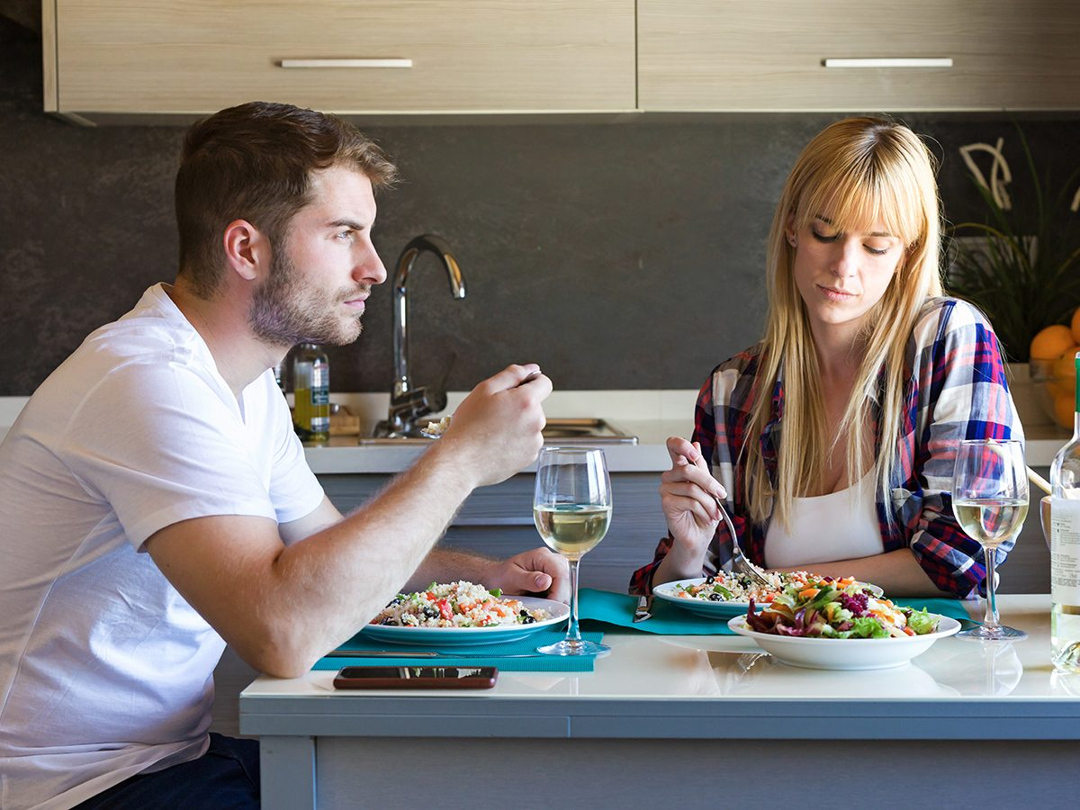 Shot of serious and unhappy young couple eating quinoa salad in the kitchen at home.