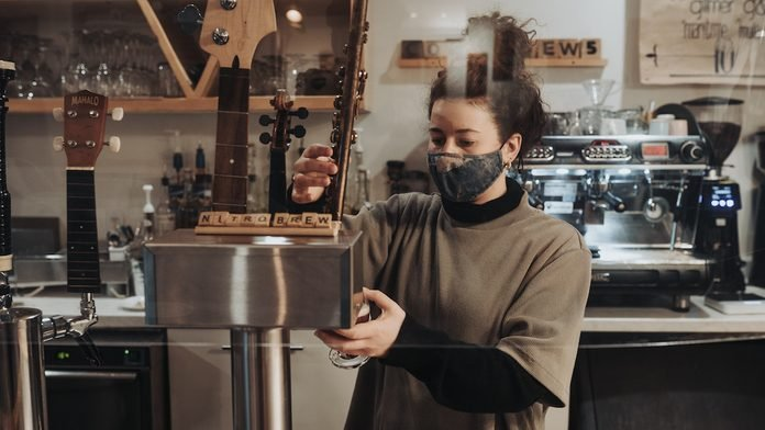A barista makes a coffee drink at Tipsy Muse Cafe