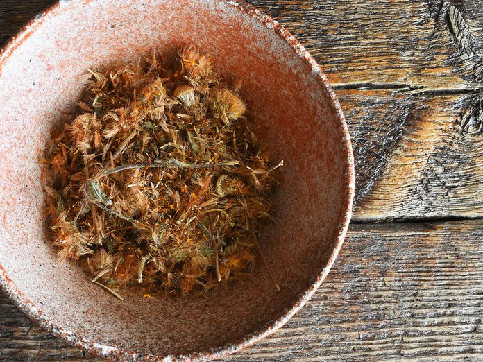 A top view image of dried Arnica herbs in a decorative pottery bowl.