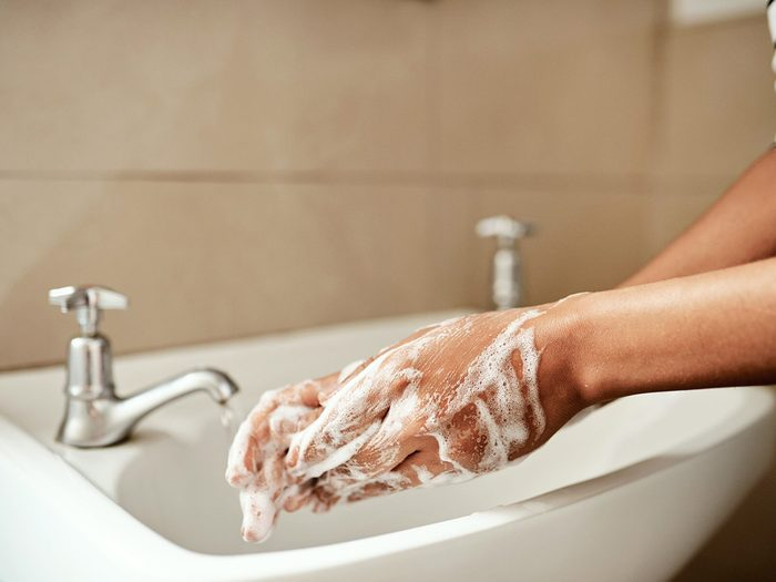 Cropped shot of a woman washing her hands with soap in the bathroom sink at home