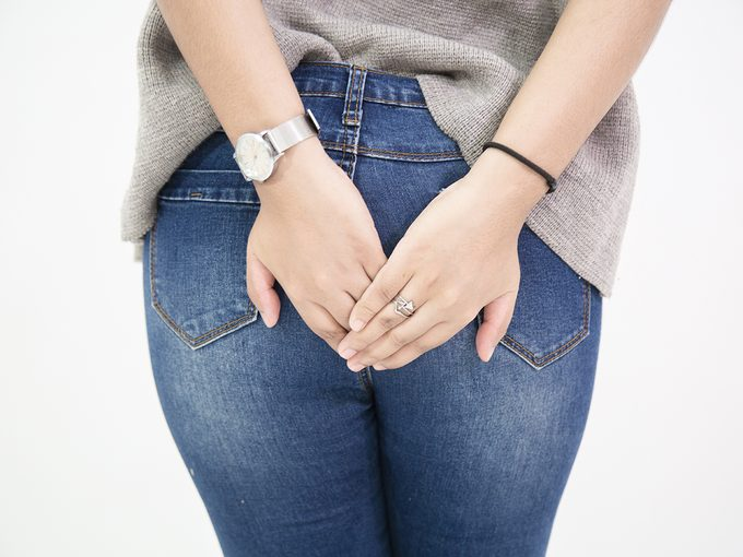 Holding in farts - woman covering her bum