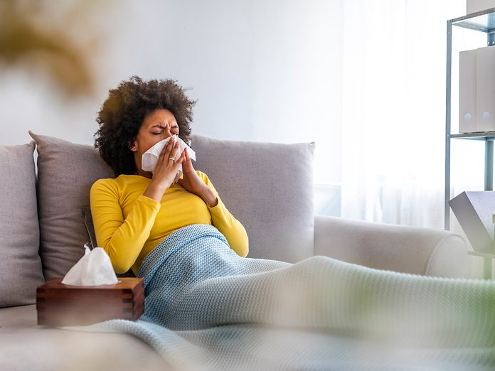 Picture showing sick woman sneezing at home. Young sick woman sneezing in tissue sweating from flu fever. Sick woman catch cold. Sneezing with handkerchief, coughing, got flu, having runny nose.