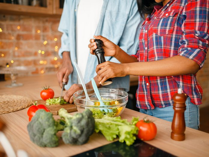 Black couple cooking together on the kitchen