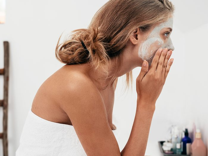 Side view shot of woman applying face mask.