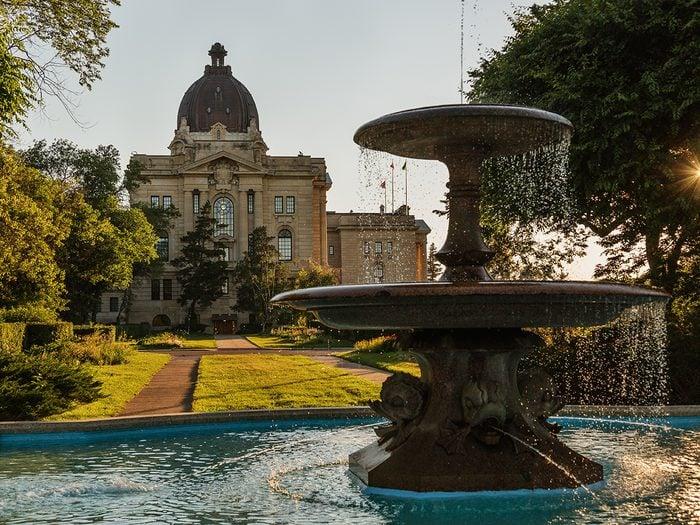 Historical Places in Every Province - Regina, Saskatchewan, Canada - June 2020: Ornamental stone fountain with the Saskatchewan Provincial Legislative Building in the background located in Wascana Park