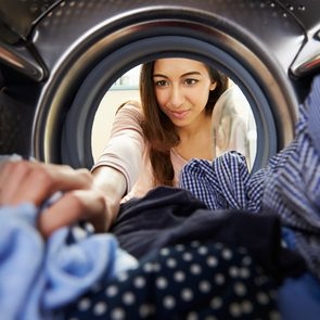 Never do this to your washer and dryer - woman reaching inside dryer