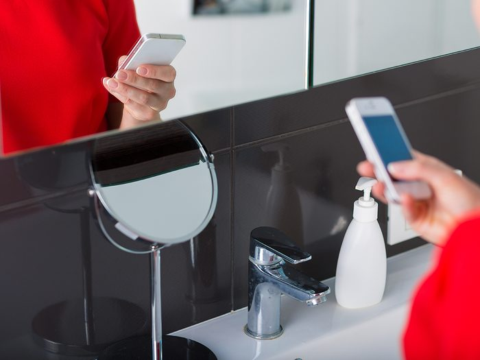 Woman standing by the mirror and holding a cell phone