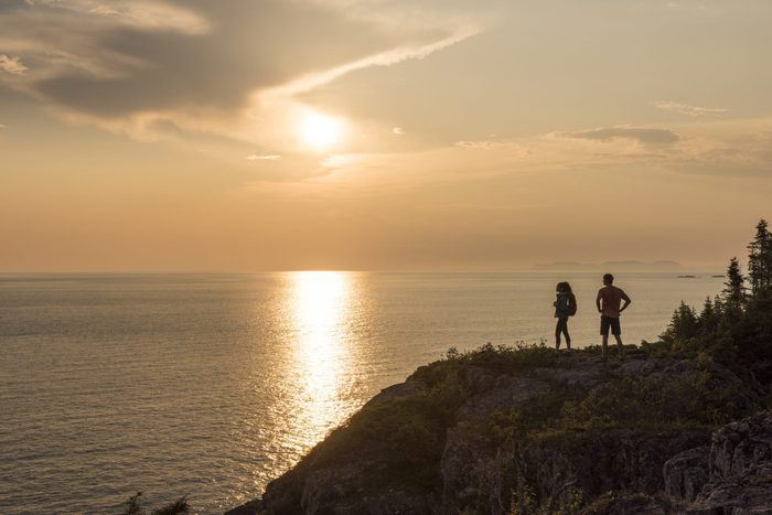 """Best place to watch the sunset in every province - Visitors hiking the Manitou Miikna, """"the spirit trail"""", at rocky outlook area at sunset. Pukaskwa National Park"""