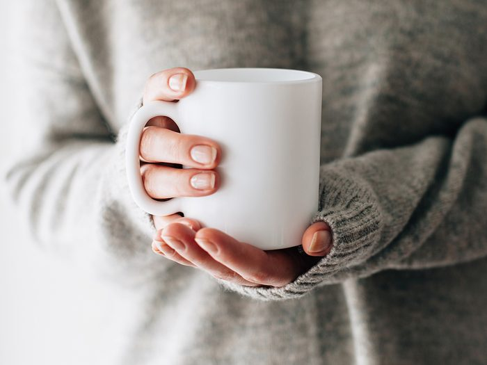 Do You Need to Wash Your Coffee Mug Every Day - Closeup of female hands with a mug of beverage. Beautiful girl in grey sweater holding cup of tea or coffee in the morning sunlight