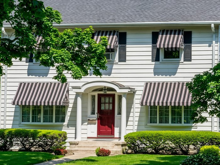How to cool down a room without AC - house with striped awnings