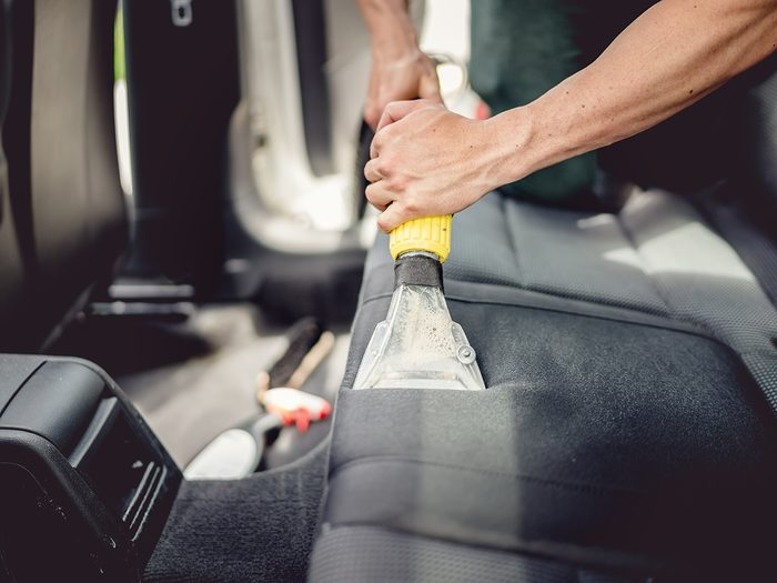How to clean car seats - Car detailing and car care concept - Professional using steam vacuum for draining stains