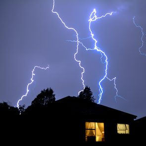 Severe weather - Cloud to Ground Urban Lightning, Lighting Up House Rooftops Silhouetting in foreground.
