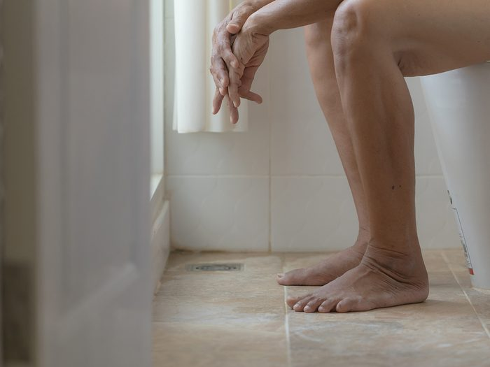 Burns when I pee - Closeup legs of woman sitting on toilet