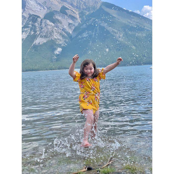 Candid photography - little girl splashing in mountain lake