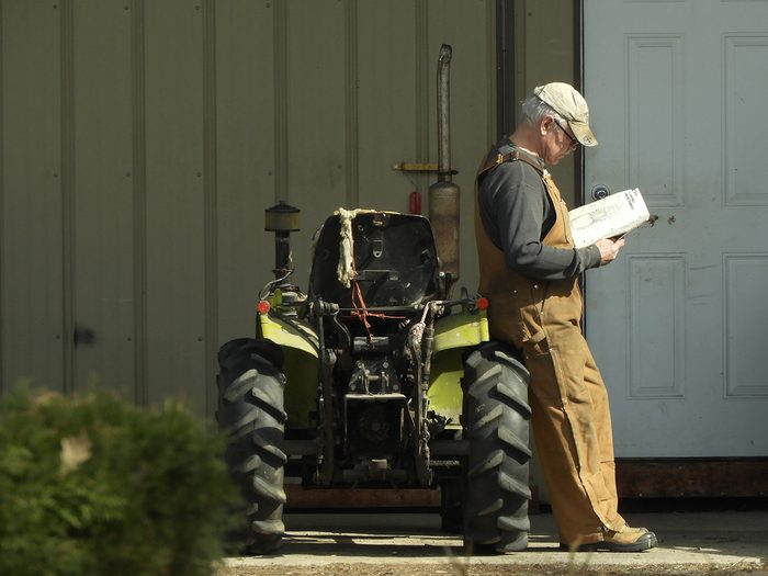 Candid photography - Man reading beside tractor