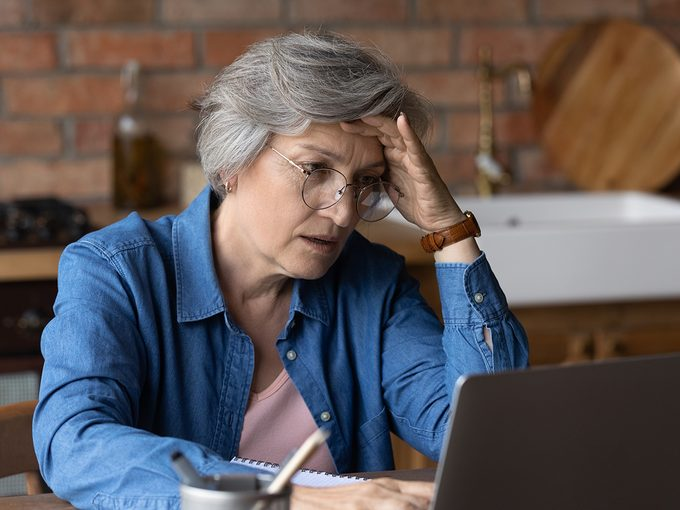 Facebook marketplace scams - Distressed mature grey-haired woman look at laptop screen have problems pay household bills or taxes online. Unhappy stressed senior female in glasses troubles with computer slow internet or spam.