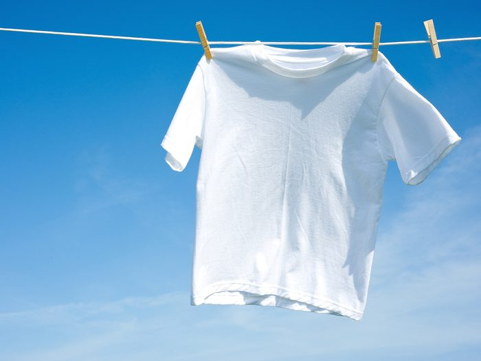 How to unshrink clothes - A plain white T-shirt hanging on a clothesline on a beautiful, sunny day