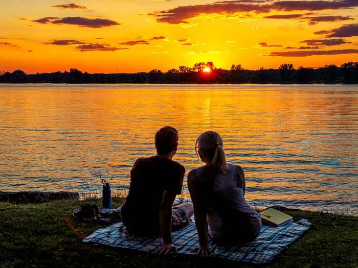 Sunset pictures - couple on lakeshore watching sunset