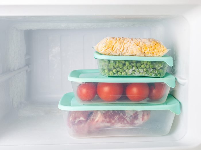 This is why there isn't a light in your freezer - Frozen vegetables and meat in blue plastic containers. Frozen corn, peas, tomatoes, meat. Cold freezer