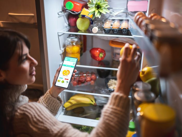 Keep your food from spoiling - Beautiful young woman standing next to an opened refrigerator door, holding a smart phone and ordering fresh fruit and vegetables online for home delivery