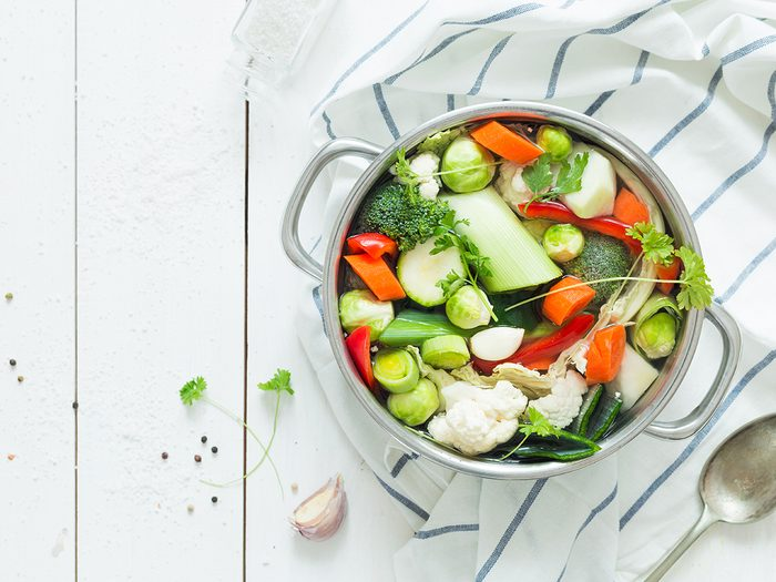 Various fresh vegetables in a pot - colorful fresh clear spring soup (vegetarian bouillon or stock). Rural kitchen scenery from above (top view). White wooden background - layout with free text space.